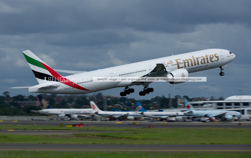 Emirates B777-300/ER takes off, with rivals Singapore Airlines, Air China, China Southern and Air Canada waiting at the gates in the background.