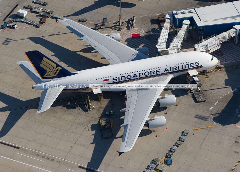 The Singapore Airlines Airbus A380 is seen here parked at the gate at Sydney Airport with multiple jetways connected to it.