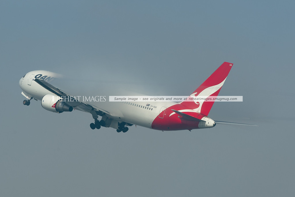 A Qantas B767-338/ER takes off from Sydney as the fog starts to lift. But it still formed impressive condensation over the wings. Most of the plane is obscured by the condensation.