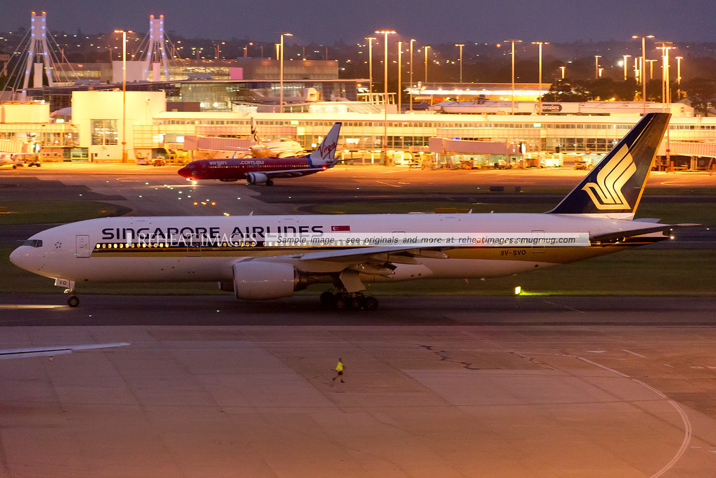 Singapore Airlines B777-212/ER taxiing out to Sydney airport runway 16 right at dusk.