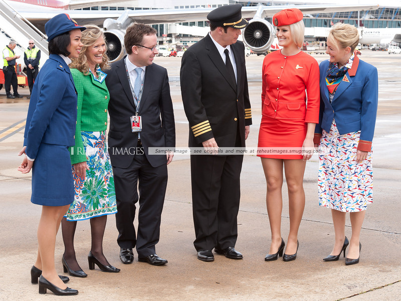 John Travolta and Qantas' Alan Joyce pose for the cameras with staff modelling the classic uniforms that represent the long history of Qantas. Mr Travolta attended the Qantas 90th anniversary celebrations, bringing his 1964 Qantas Boeing 707-138B with him.