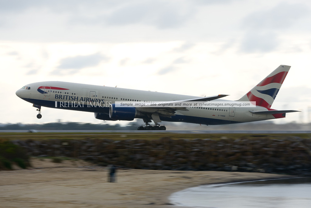 British Airways B777-236/ER takes off from Sydney airport during a passing rain shower.