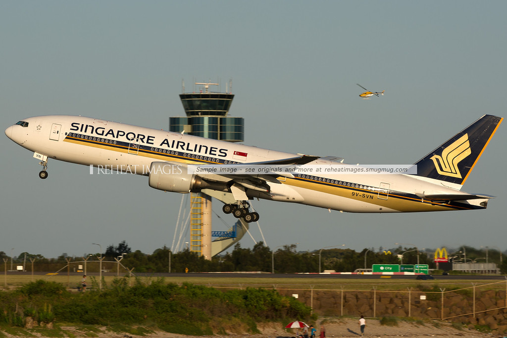 A Singapore Airlines Boeing 777-212/ER departs Sydney airport on runway 34 left - passing in front of the air traffic control tower.