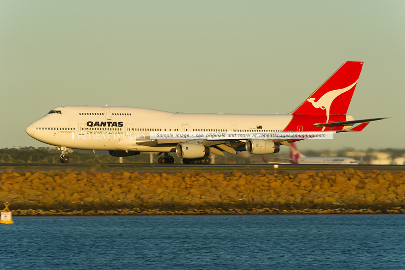 A Qantas Boeing 747-438 departing Sydney airport on runway 34L. A company B737-800 is in the background.