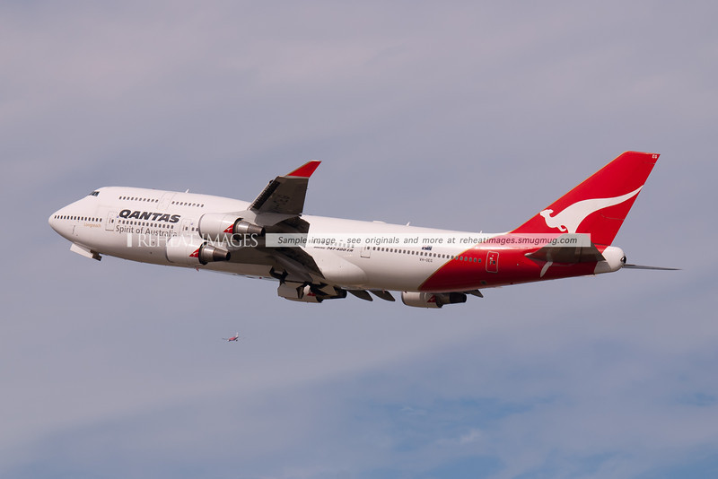 A Qantas Boeing 747-438/ER leaves Sydney airport, while a Virgin Blue plane is seen in the background having departed on runway 34 right.