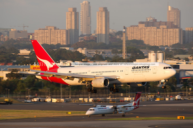 A Qantas Boeing 767-336/ER arrives at Sydney airport on runway 16 right. A QantasLink Dash 8 Q400 is seen in the background.