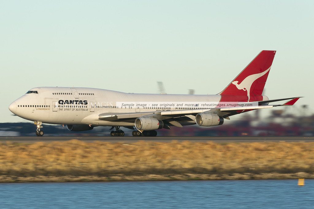 A Qantas B747-438 takes off from Sydney airport at sunset. Low shutter speed is used to blur the foreground and background details.