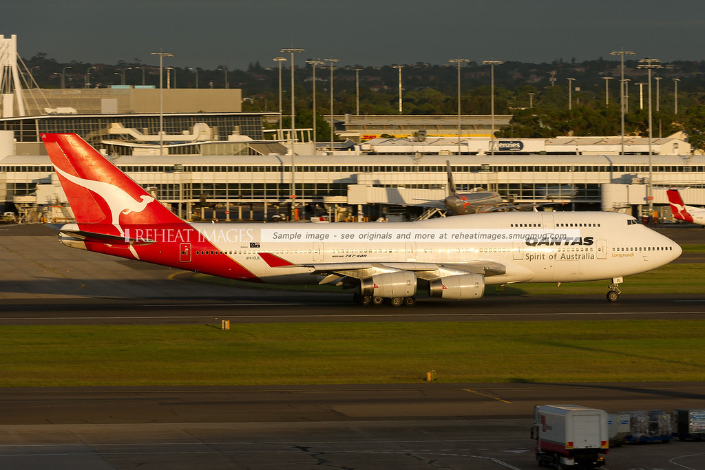 A Qantas Boeing 747-438 departing Sydney airport on runway 16 right at sunset. The domestic terminal is visible in the background.