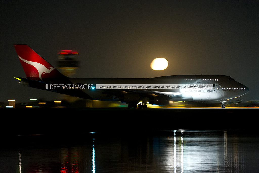 Qantas 21 Boeing 747-400 VH-OJL on the way out to runway 34 left at Sydney airport. The moon is seen in the background.