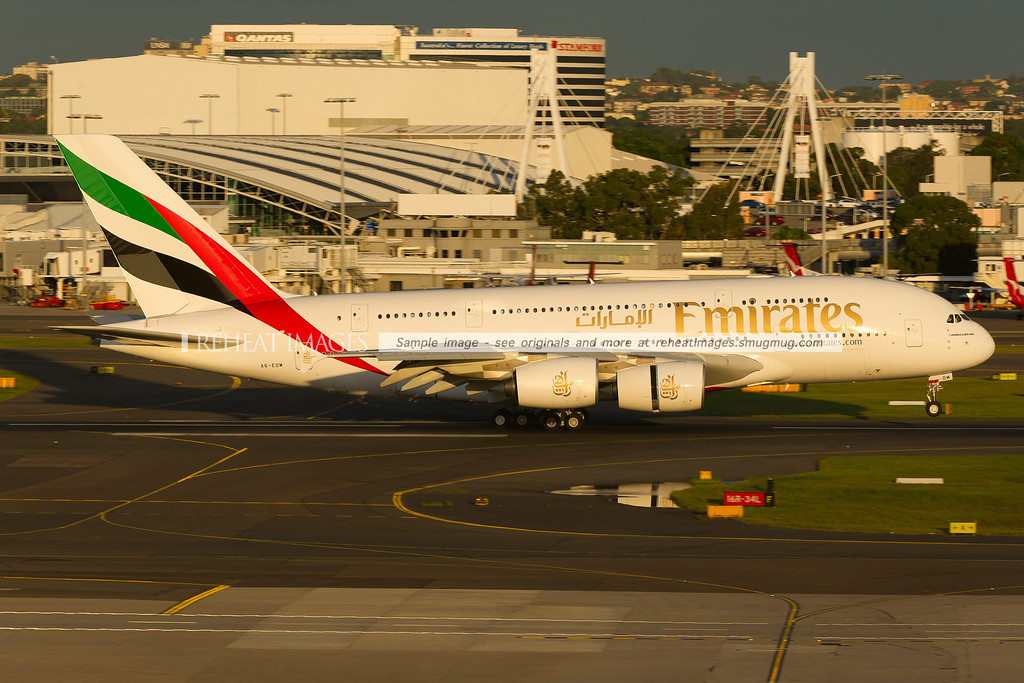 An Emirates Airbus A380-861 lands on runway 16 right at Sydney airport. The domestic terminal is seen in the background.