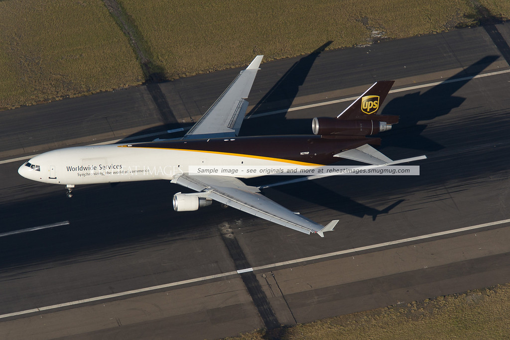 A UPS McDonnell Douglas MD-11F lands at Sydney airport, seen from above as it touches down.