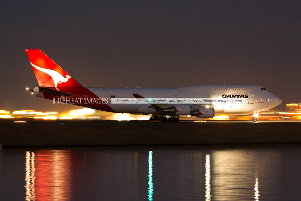 A Qantas B747-438/ER lights up the calm waters of Botany Bay at night, with the lights of Port Botany blurred in the background by 1/4 second shutter speed.