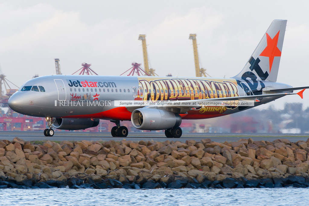 "This Jetstar Airbus A320 wears decals promoting various charities and the group final tour ""Sunsets"" of the iconic group Powderfinger. The afternoon sun is setting on this plane."