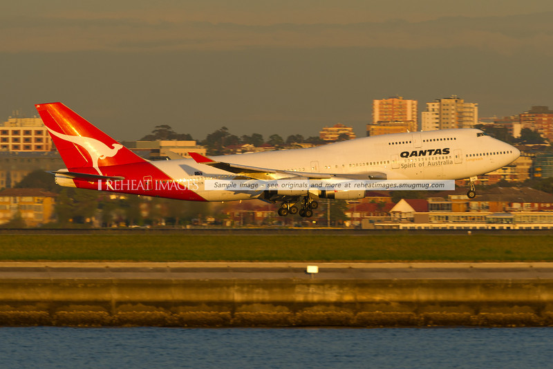 A Qantas Boeing 747-438 is landing at Sydney airport runway 34 left against the backdrop of Brighton-Le-Sands. The plane is powered by four Rolls Royce RB-211 engines.