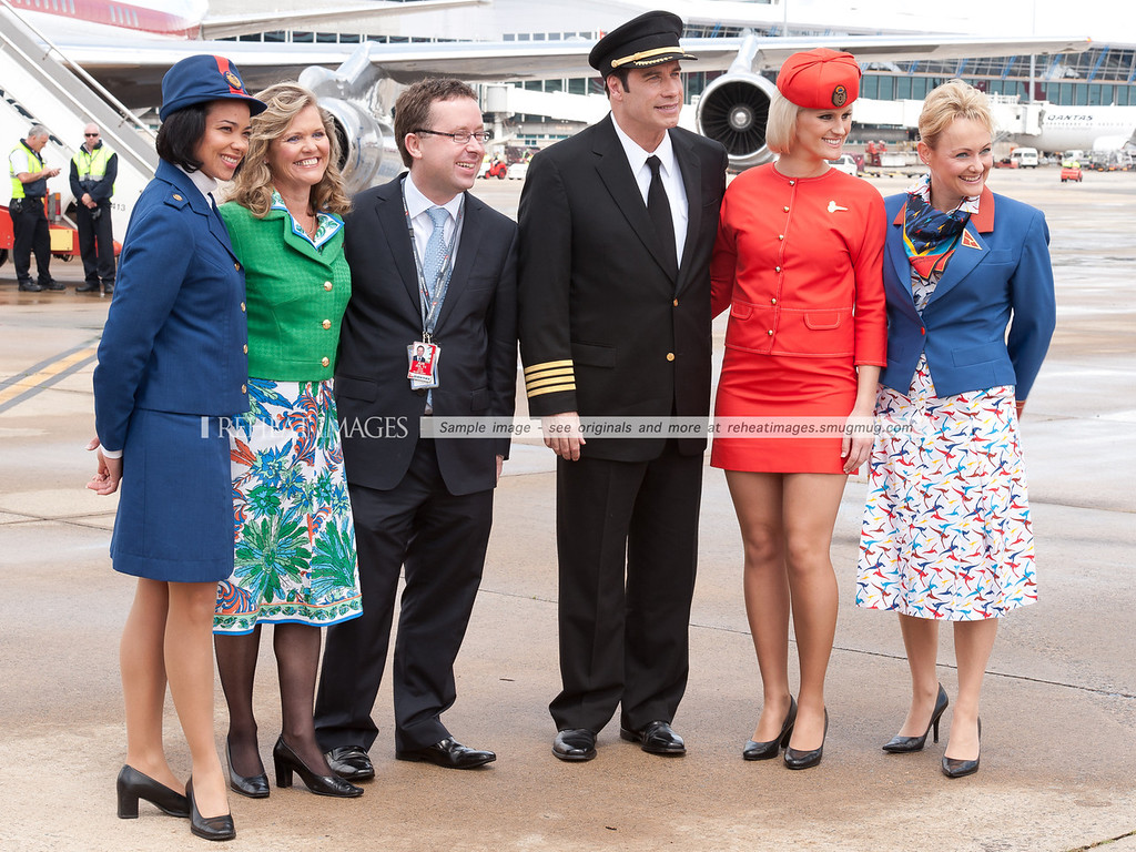 John Travolta and Qantas' Alan Joyce pose for the cameras with staff modelling the classic uniforms that represent the long history of Qantas.