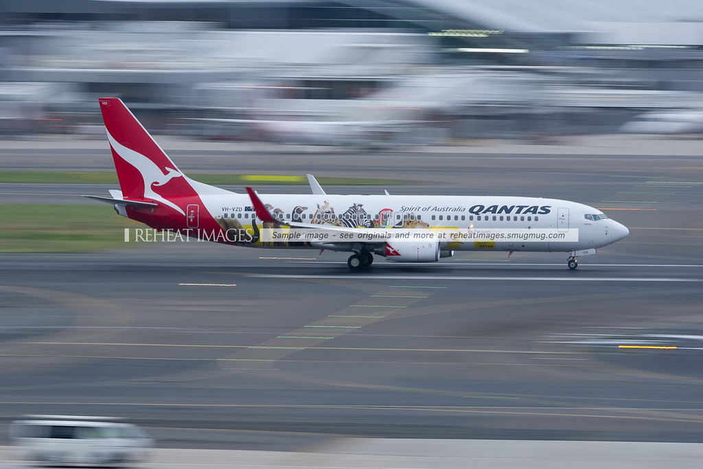 A Qantas Boeing 737-838 wearing a promotional colour scheme for Qantas/Optus frequent flyer partnership takes off from Sydney airport.