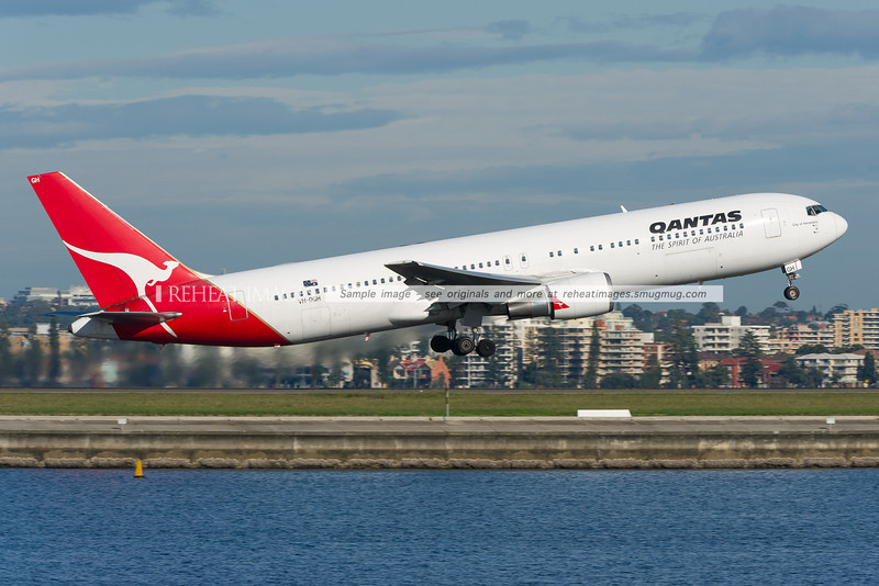 "A Qantas Boeing 767-338/ER VH-OGH ""City of Parramatta"" departs Sydney airport on runway 34 right. Brighton-Le-Sands is seen in the background."