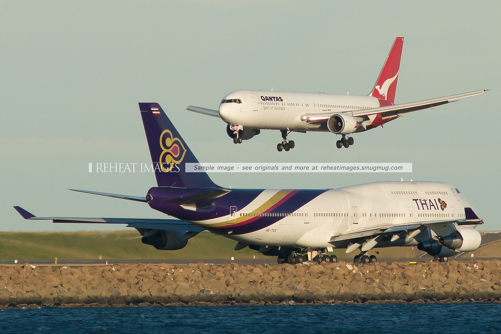 Qantas B767-338/ER landing while a Thai B747-4D7 waits to turn onto runway 34 left.