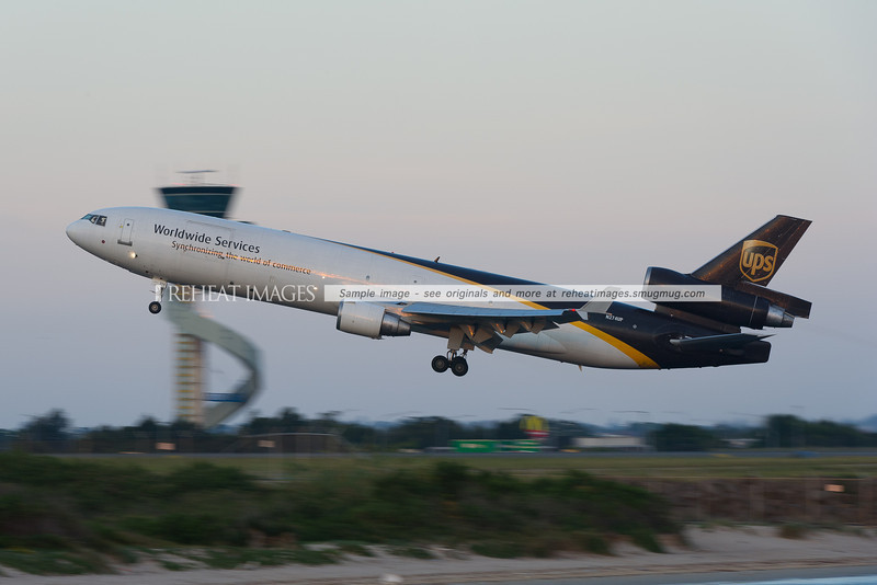 McDonnell-Douglas MD-11F of United Parcel Service takes off from runway 34 left at Sydney airport with the air-traffic control tower in the background blurred by low shutter speed panning effect.