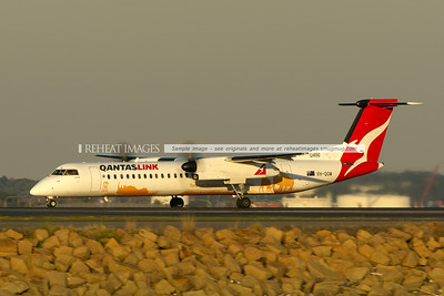 A QantasLink Bombardier Dash-8 Q400 takes off from Sydney airport at sunset. It is carrying a special colour scheme for Taronga Western Plains Zoo.
