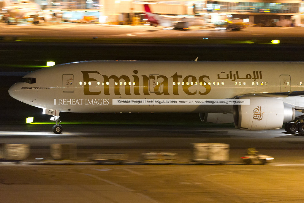 Emirates B777-31H/ER taxies out to runway 16R at night.