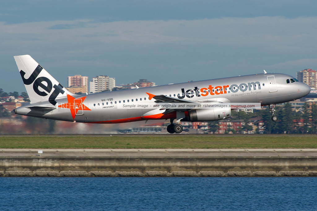 A Jetstar Airbus A320-200 leaves Sydney airport on runway 34 right. In the background is Brighton-Le-Sands.