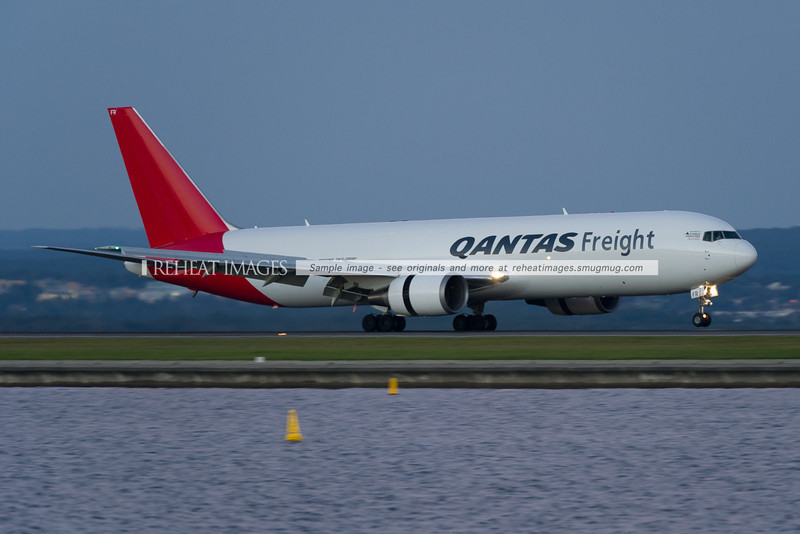 A Qantas Freight (Express Freighters Australia) Boeing 767-381F/ER lands on runway 34 right at Sydney airport, early in the morning.
