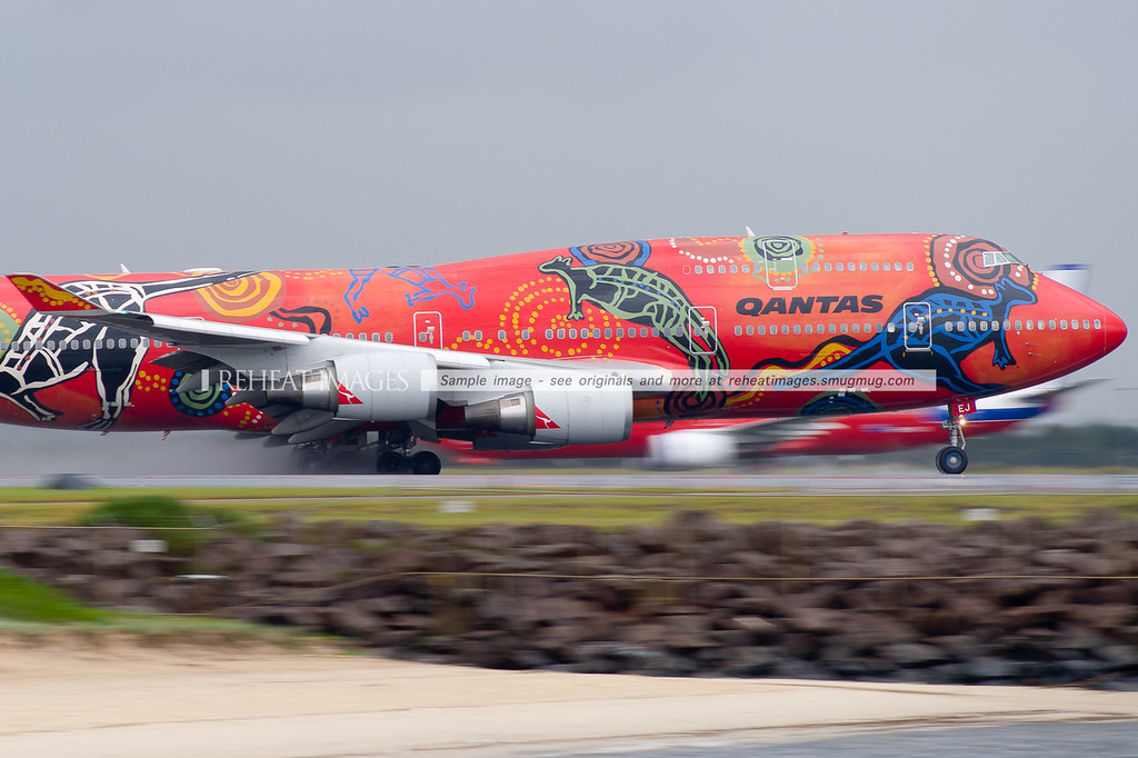 Qantas' most iconic Boeing 747, named Wunala Dreaming, takes off from runway 16 right at Sydney airport on a very wet and rainy day. The vibrant colour scheme is courtesy of the Balarinji Design Studio. The scheme has adorned two B747 planes, this being the second of the two.