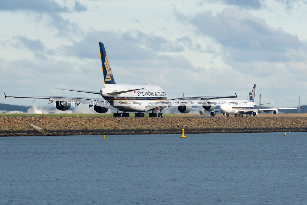 Singapore Airlines A380-841 and the company B747-412 Freighter are seen together at Sydney airport. The Freighter is just commencing takeoff.