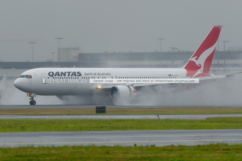 A Qantas Boeing 767-338/ER throws up large amounts of water with its reverse thrust as it attempts to slow down on a very wet runway 16 right at Sydney airport.