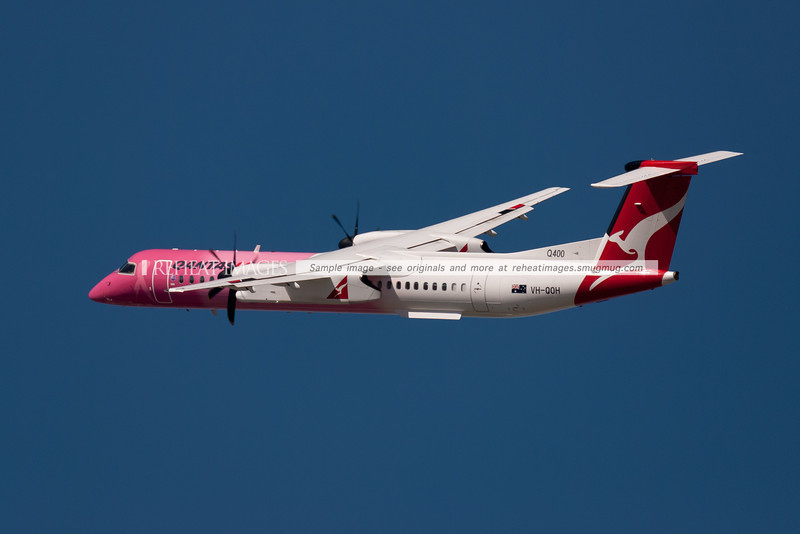 A QantasLink Dash 8 Q400 departs Sydney airport. This one is wearing a special colour scheme in honour of cancer research.