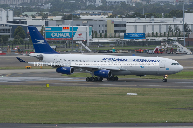 An Aerolineas Argentinas Airbus A340-200 leaves Sydney airport. In the background are Airbus A330 and A380 planes from Qantas.