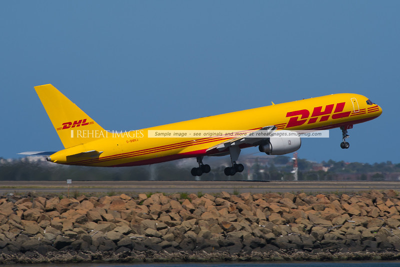 DHL's Boeing 757 freighter takes off from runway 34 left at Sydney airport. This plane replaced the memorable B727-200 freighter VH-DHE. The old B727 was always memorable for its thundering noise and the ever present trail of smoke from its exhausts.