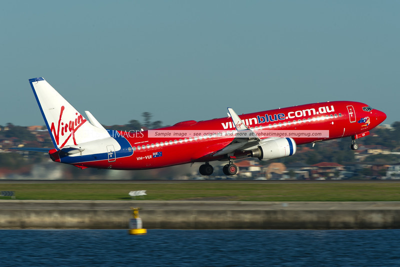 A Virgin Blue Boeing 737-800 takes off from runway 34 right at Sydney airport.