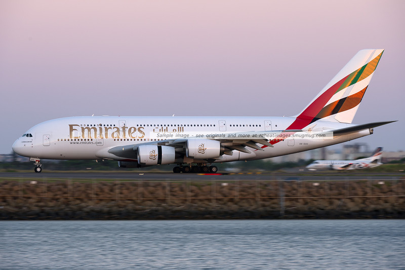 An Emirates Airbus A380-861 lands on runway 34 left at Sydney airport, with a small Regional Express Saab 340 in the background as a reminder of the massive size of the A380 - currently the worlds largest passenger plane.