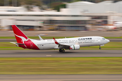 A Qantas B737-838 lands at Sydney airport, against the backdrop of the domestic terminals, blurred by low-shutter speed panning effect.