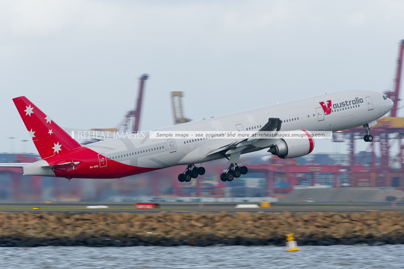 V Australia's B777-3ZG/ER takes off from Sydney airport with the containers and cranes of Port Botany in the background, blurred by the low shutter speed.