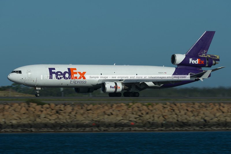 FedEx MD-11F slowing down after landing at Sydney airport. Note the paint missing around the back of the plane.