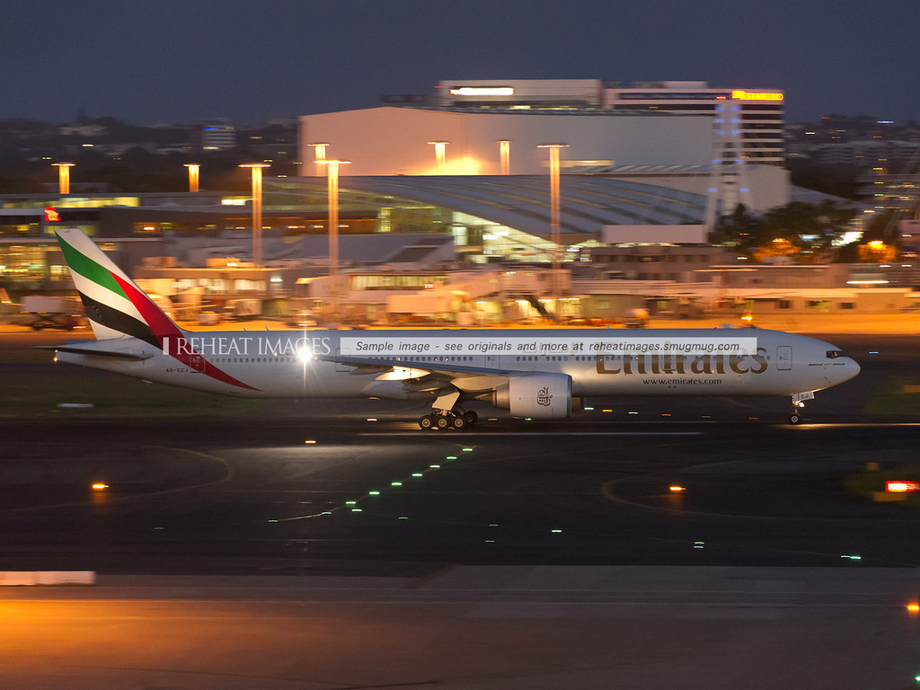 Emirates B777-300/ER takes off from Sydney airport at dusk.