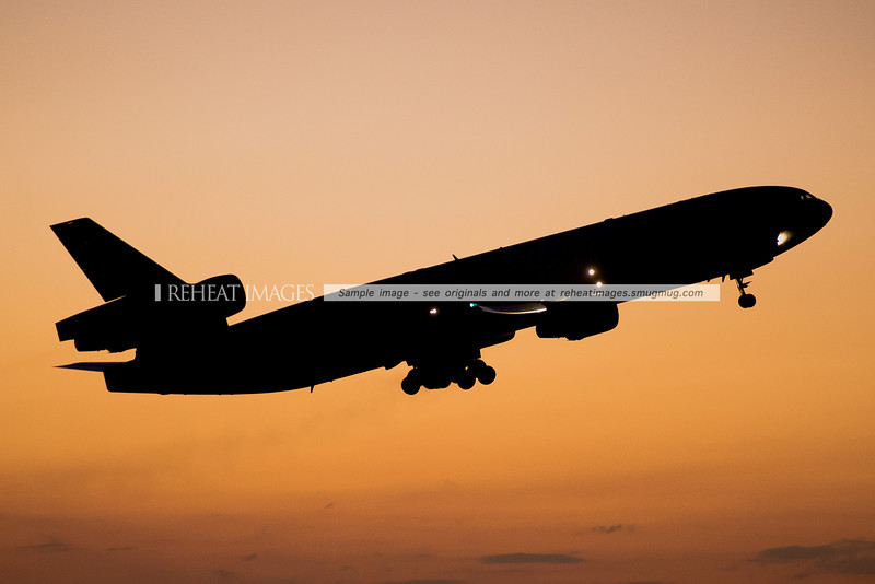 The silhouette of a McDonnell Douglas MD-11F departing Sydney airport at dusk.