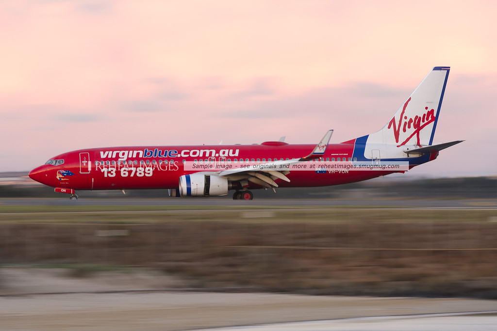 Virgin Blue B737-800 has just landed at Sydney airport and is still slowing down. Low shutter speed blurs the background and foreground details.