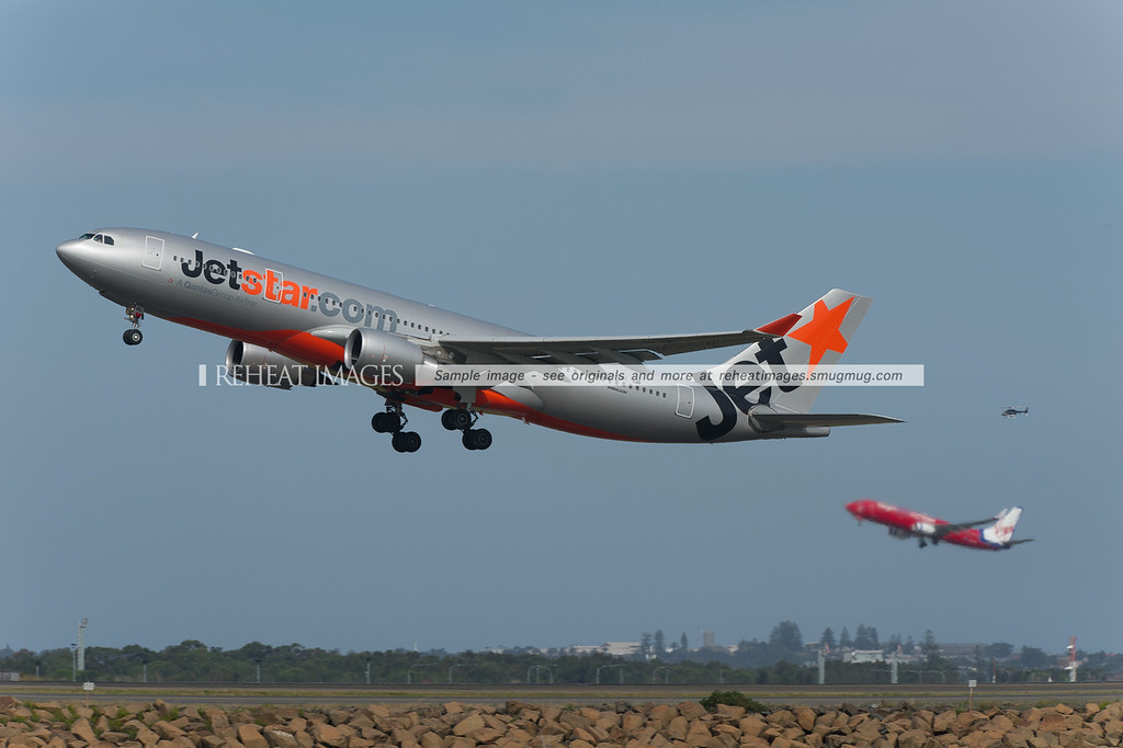 A Jetstar Airbus A330 takes off from Sydney airport with a Virgin Blue B737 doing the same in the background, while a helicopter is also out and about.