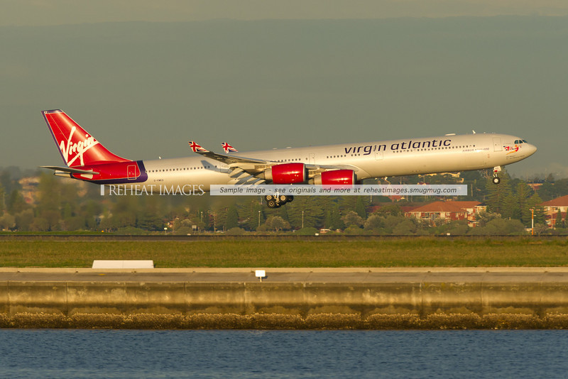Virgin Atlantic A340-642 is landing at Sydney airport runway 34 left against the backdrop of Brighton-Le-Sands.