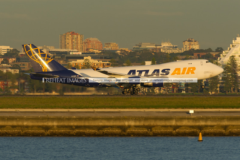 Atlas Air Boeing 747-400 Freighter flying for Qantas is landing at Sydney airport runway 34 left against the backdrop of Brighton-Le-Sands.