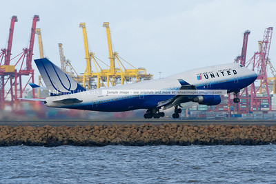 A United Airlines Boeing 747-422 takes off from Sydney airport with the containers and cranes of Port Botany in the background.