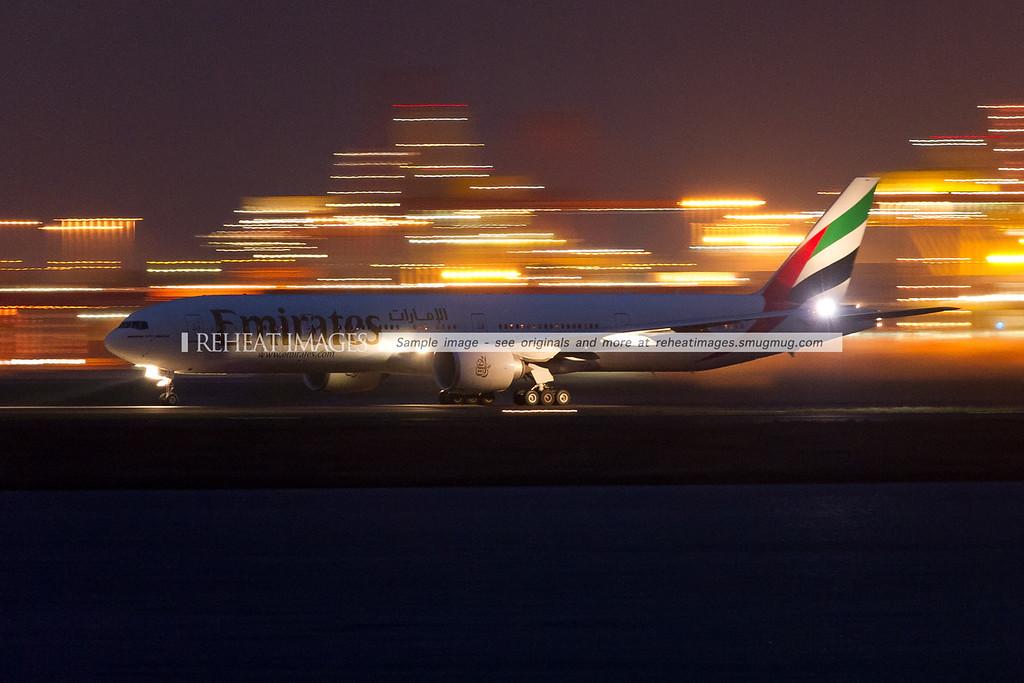 An Emirates Boeing 777-300/ER departs Sydney airport at night, set against the motion blurred lights of Port Botany.