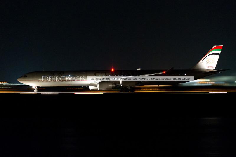 Etihad A340-642 lands at night.