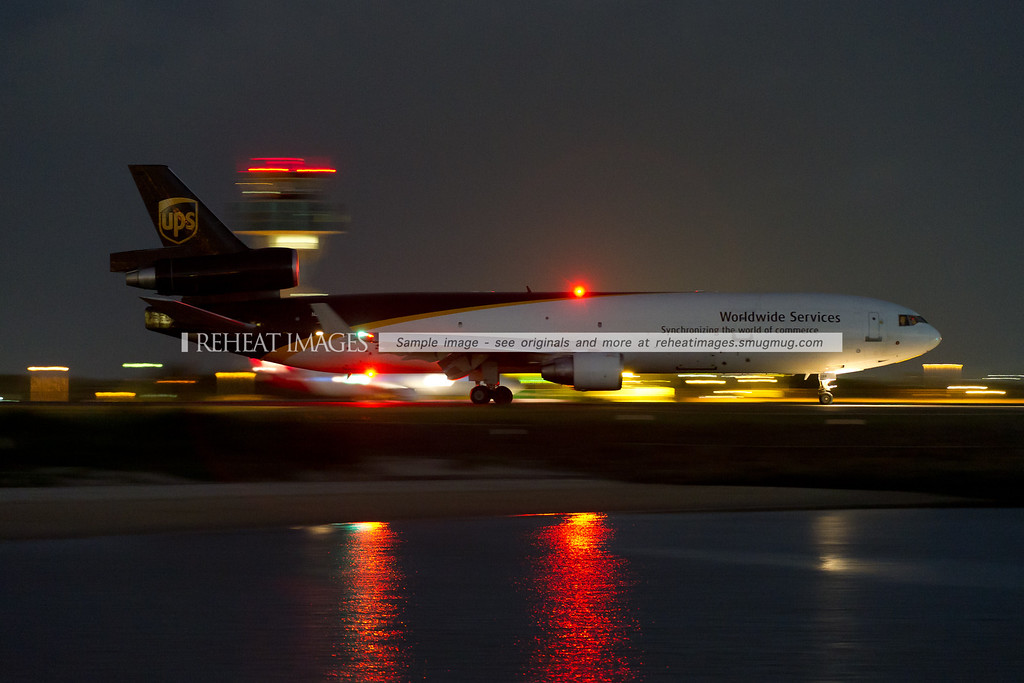UPS McDonnell-Douglas MD-11F taxiing out to runway 34 left at night. A slow shutter speed and high ISO sensitivity make it possible to see the plane easily at night.