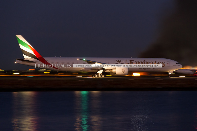 Emirates Boeing 777-300/ER A6-ECJ taxies out to runway 34 left with smoke in the background from fire training.