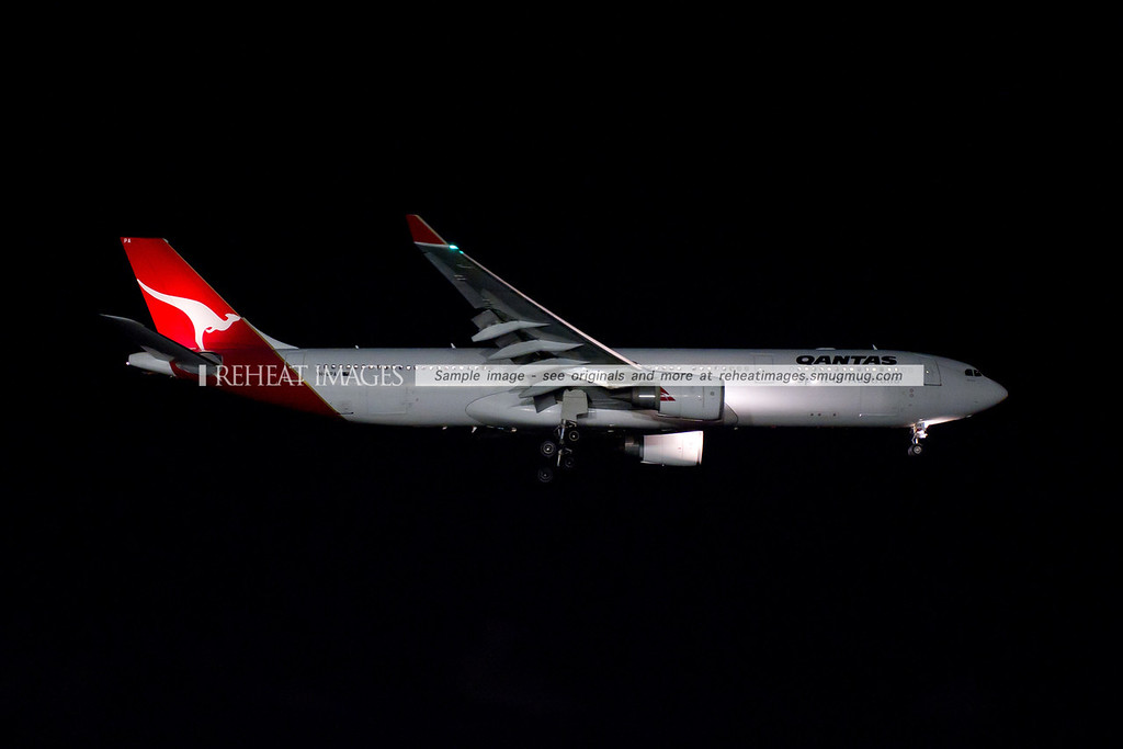 A Qantas Airbus A330-300 lands at Sydney Airport at night.